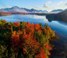Boreas Pond island fall foliage with canoeist and High Peaks range