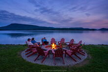Lake Pleasant Lodge lakeside campfire ring and Adirondack Chairs circle in evening