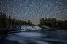 Lampson Falls on the Grass River and springtime flow eddies under star trails and shooting stars