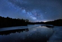 Milky Way over Sawtooth Range and Second Pond with late winter ice channel