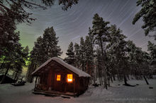 Aurora borealis and startrails over a cabin in Sweden
