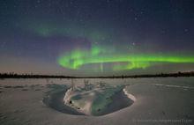 Aurora borealis above the snowy landscape near Kiruna, Sweden