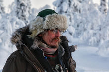 A dogsled guide gazes into the wintry wilderness