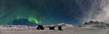 Aurora borealis display over cabins in Abisko, Sweden