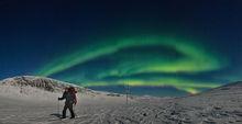 Cross country skiier under the aurora borealis in Abisko, Sweden