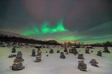 Aurora borealis display over cairn rock piles