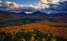 Mt Van Hoevenberg summit view over fall foliage and High Peaks with storm clouds