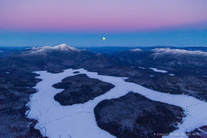 Lake Placid and Whiteface Mt with rising full moon in winter - aerial
