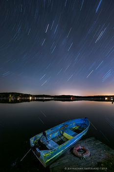 Galway Lake old flaking life-ring and rowboat on a dock under long-exposure startrails