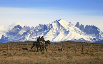 Gauchos on horseback by Torres del Paine