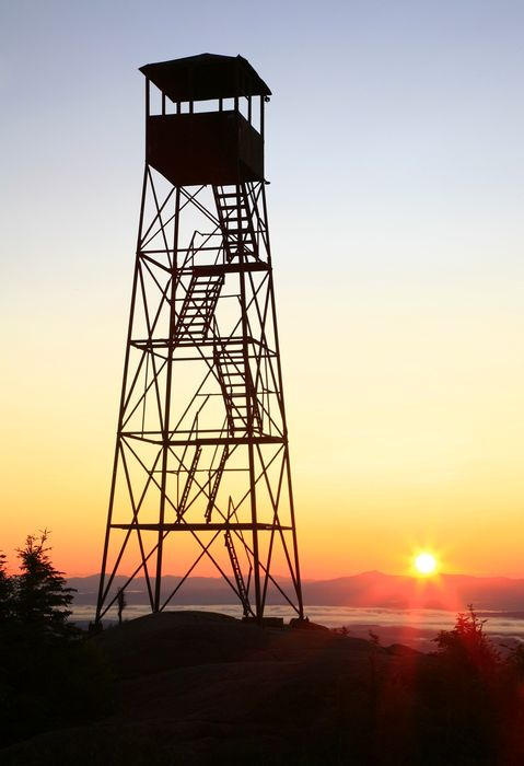 The historic Hurricane Mountain firetower, now abandoned, sillouetted by a rising sun over Camel's Hump, Vermont. The Champlain...