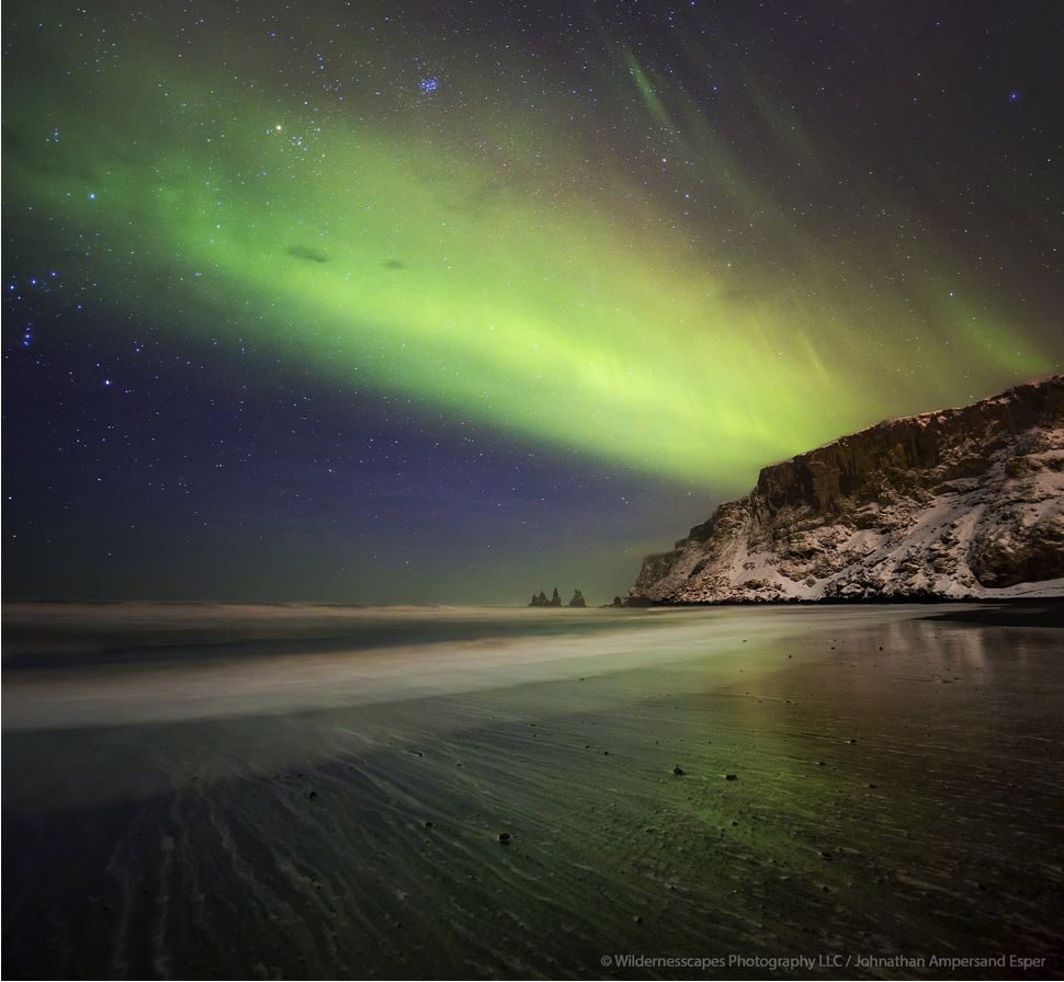The Aurora Borealis over the Reynisdrangar sea stacks from the town of Vik's beach, Iceland.