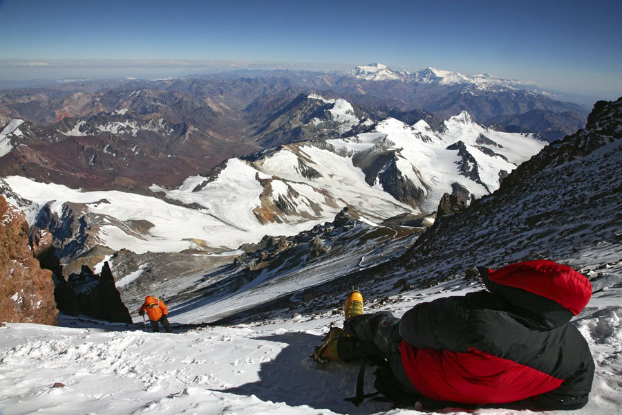 An exhausted climber rests and waits for a team member on summit day high on Aconcagua, the highest mountain in South America...