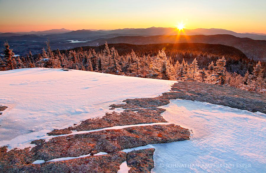 Mt. Morris summit rock patterns mirroring the layers of Adirondack mountains and High Peaks range in the eastern sky on a...
