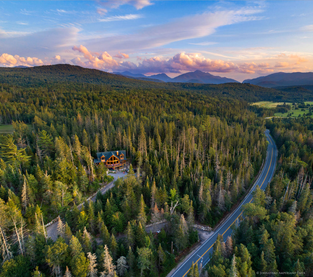 the scenic River Road and a log home in the town of North Elba and Lake Placid region, with the Adirondack High Peaks in background...