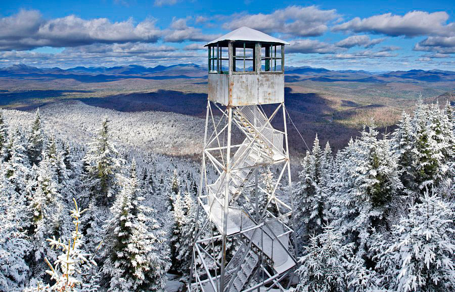 Vanderwhacker Mt. Firetower in November from a spruce Treetop, with the High Peaks behind the tower.
